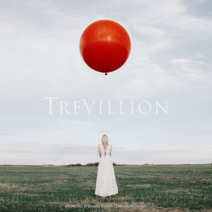 Jovana Rikalo WOMAN IN WHITE WITH LARGE RED BALLOON IN FIELD Women
