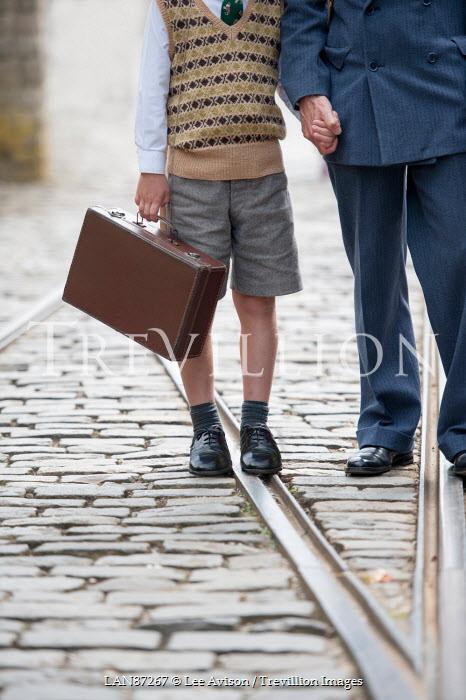 Lee Avison 1940s man holding hands with a wartime evacuee boy Men