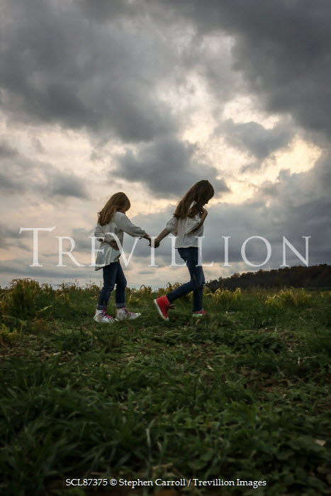 Stephen Carroll TWO GIRLS HOLDING HANDS IN COUNTRYSIDE Children