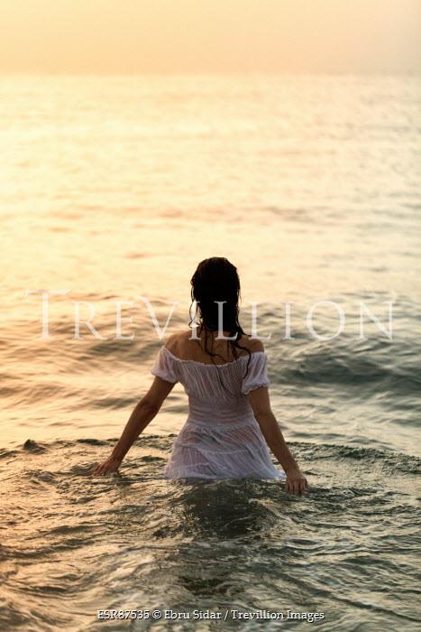 Ebru Sidar WOMAN IN WHITE DRESS IN SEA AT SUNSET Women