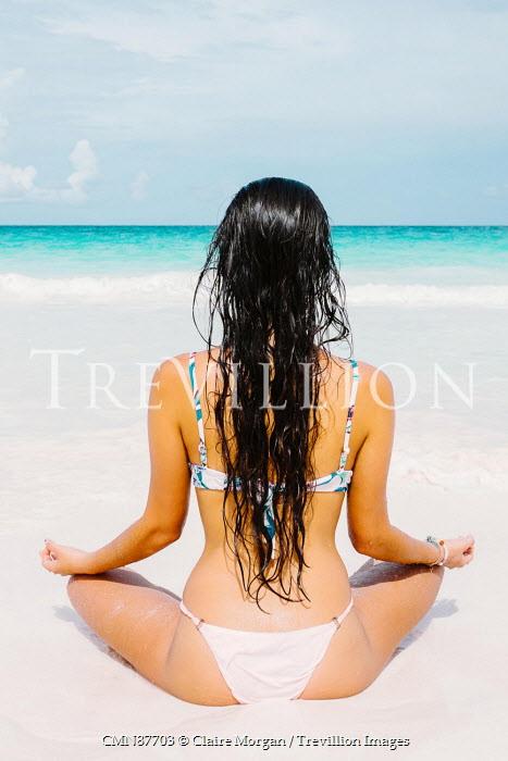 Claire Morgan WOMAN IN BIKINI MEDITATING ON BEACH Women