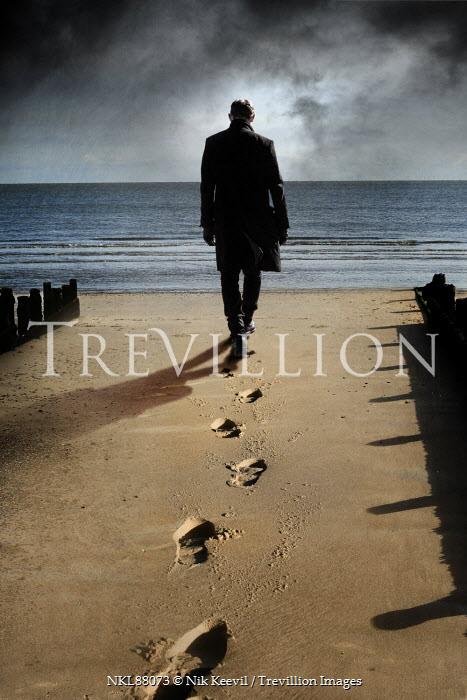 Nik Keevil MAN ON WINTRY BEACH WITH SANDY FOOTPRINTS Men