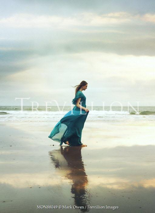 Mark Owen WOMAN IN BLUE DRESS WALKING ON CLOUDY BEACH Women