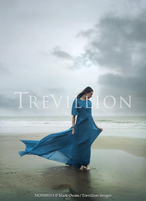 Mark Owen WOMAN IN BLUE DRESS  ON BREEZY BEACH Women