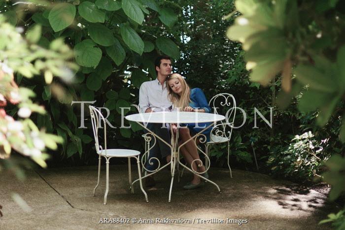 Anna Rakhvalova YOUNG COUPLE BY TABLE CUDDLING IN GARDEN Couples