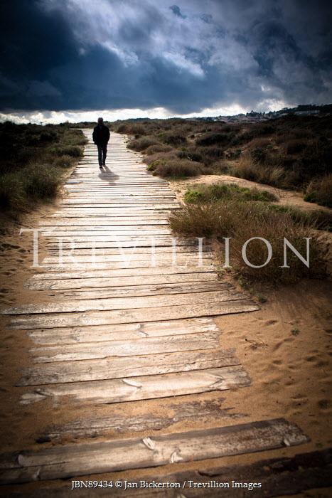 Jan Bickerton SILHOUETTED MAN WALKING ON PATH IN DUNES Men