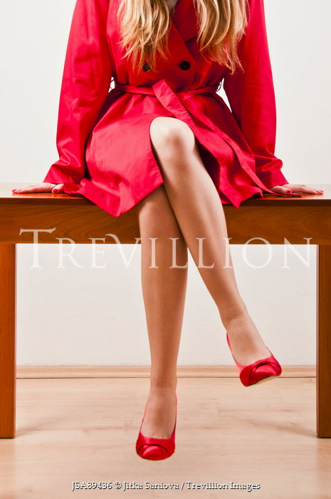 Jitka Saniova WOMAN IN RED COAT SITTING ON TABLE Women