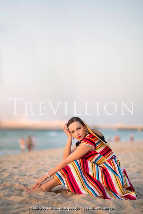 Maja Topcagic WOMAN IN STRIPY DRESS SITTING ON BEACH Women