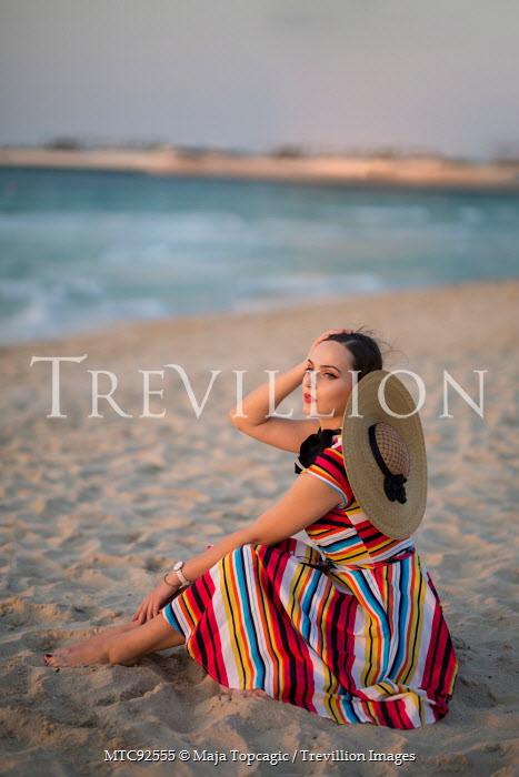 Maja Topcagic WOMAN IN STRIPY DRESS SITTING ON BEACH AT SUNSET Women