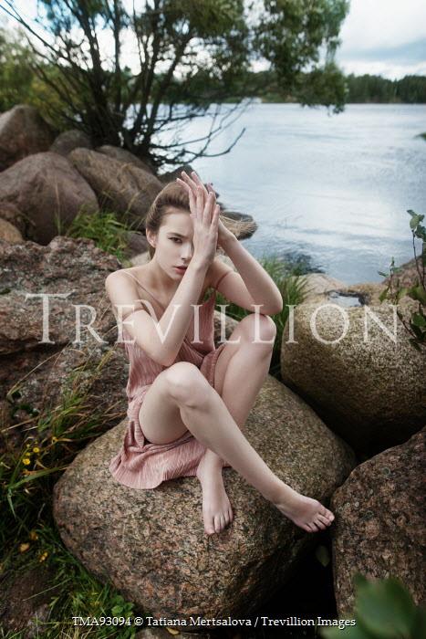 Tatiana Mertsalova YOUNG WOMAN SITTING ON ROCKS BY LAKE Women