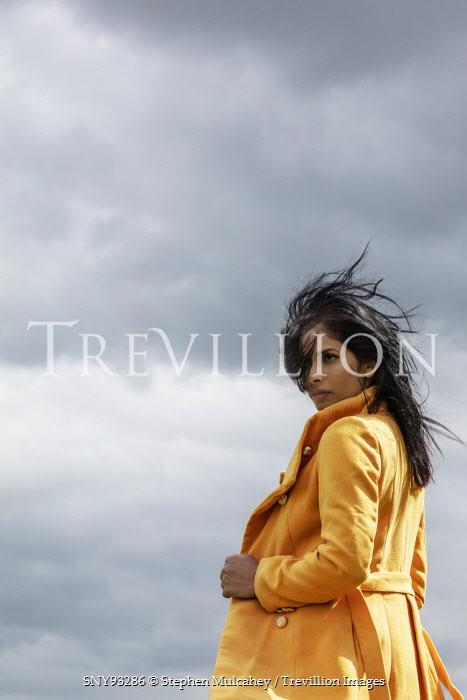 Stephen Mulcahey young woman wearing a bright yellow coat Women