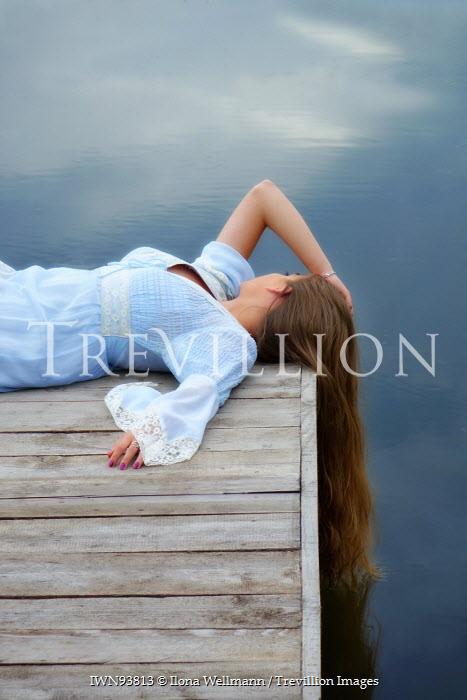 Ilona Wellmann WOMAN LYING ON JETTY BY LAKE Women