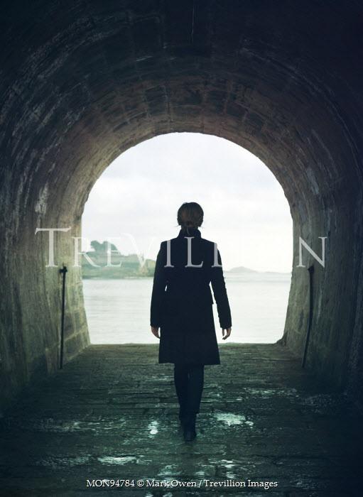 Mark Owen WOMAN WALKING IN DAMP TUNNEL Women