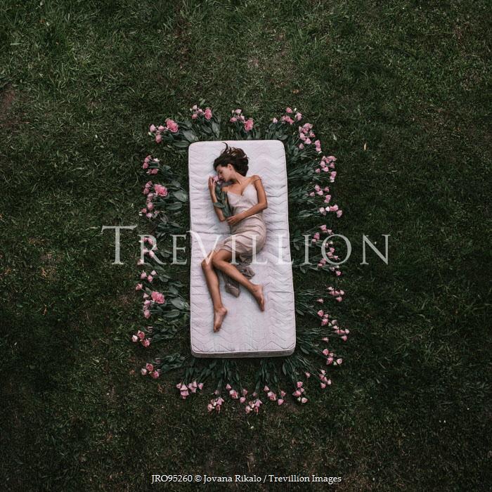 Jovana Rikalo WOMAN SLEEPING IN FIELD WITH FLOWERS Women