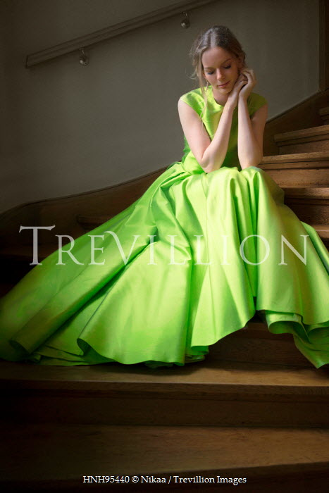 Nikaa WOMAN IN GREEN DRESS SITTING ON STAIRCASE Women
