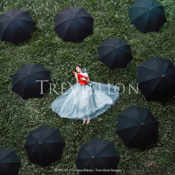 Jovana Rikalo WOMAN LYING SURROUNDED BY UMBRELLAS Women
