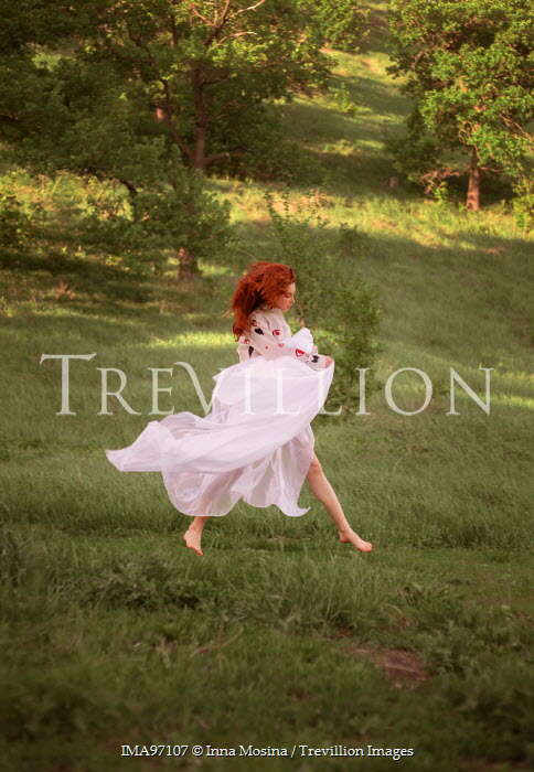 Inna Mosina WOMAN WITH RED HAIR JUMPING IN COUNTRYSIDE Women