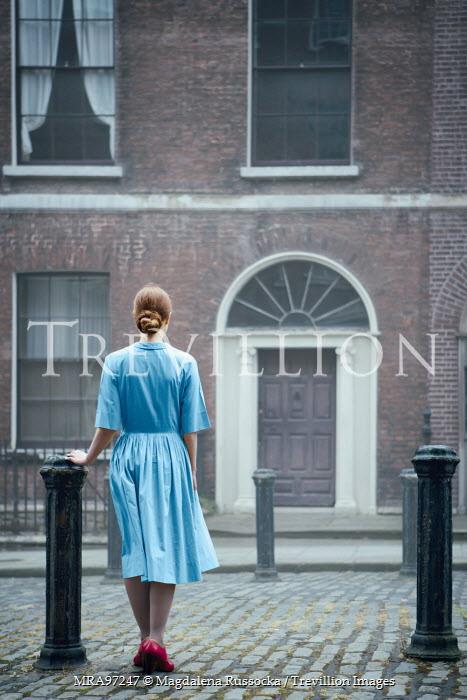 Magdalena Russocka retro woman in blue dress standing at door Women
