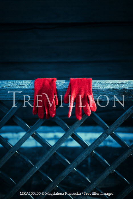 Magdalena Russocka pair of red gloves hanging on wooden fence