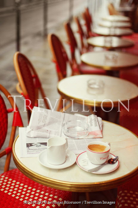 Svitozar Bilorusov COFFEE AND NEWSPAPER ON ROW OF CAFE TABLES Miscellaneous Buildings