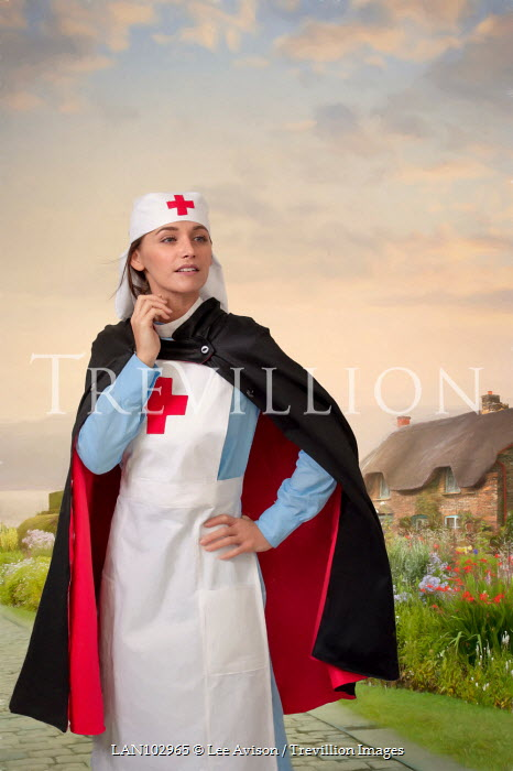 Lee Avison a vintage nurse with cape in a rural setting with thatched cottage