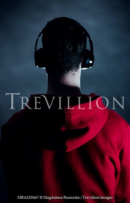Magdalena Russocka teenage boy in red hoodie with headphones inside