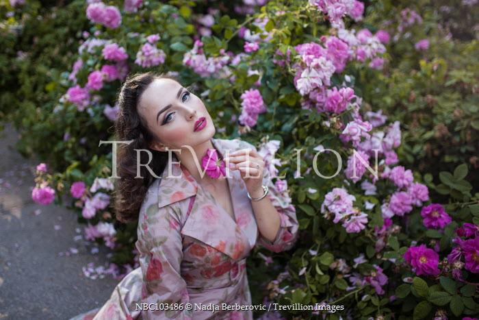 Nadja Berberovic WOMAN IN FLORAL DRESS IN ROSE GARDEN Women
