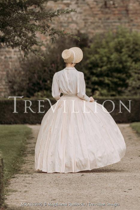 Magdalena Russocka victorian woman in straw bonnet walking in garden