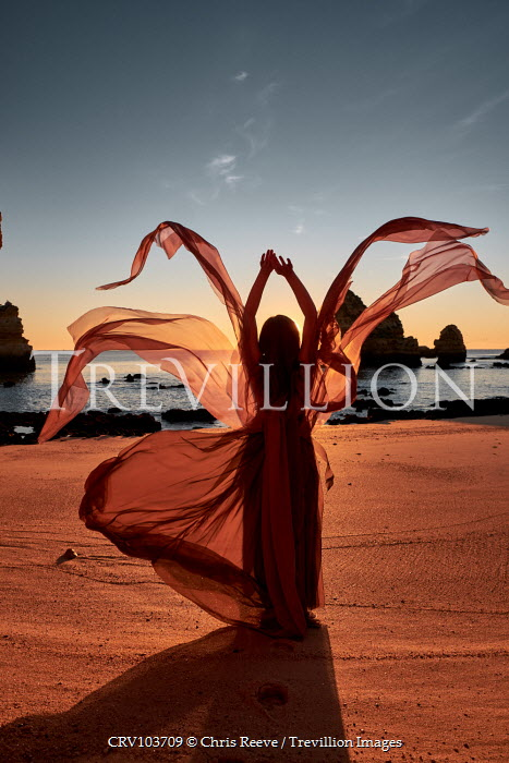 Chris Reeve WOMAN IN FLOWING SILK ON BEACH AT SUNSET Women
