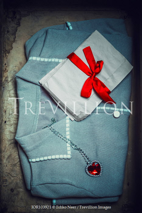 Ildiko Neer Blue blouse in suitcase with heart pendant necklace and envelops