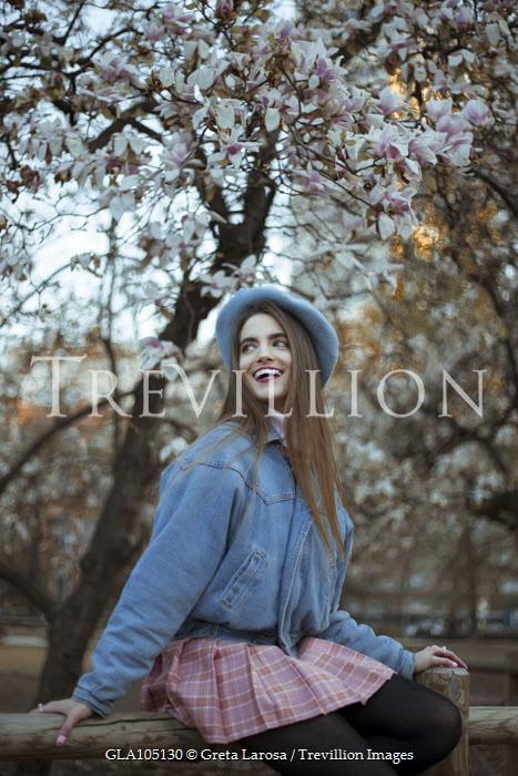 Greta Larosa SMILING GIRL SITTING ON FENCE BY MAGNOLIA TREES Women