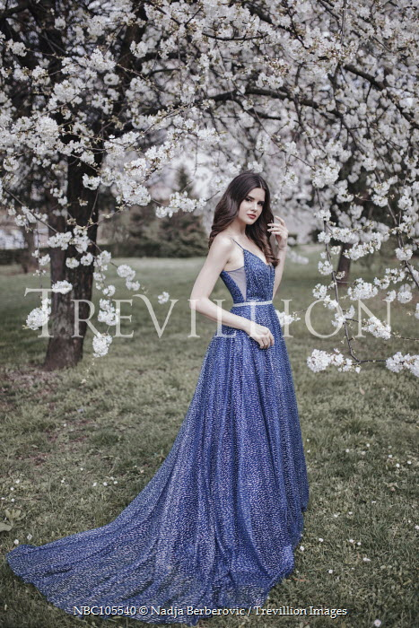 Nadja Berberovic WOMAN IN BLUE GOWN BY TREE WITH BLOSSOM Women