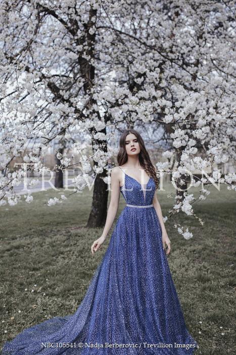 Nadja Berberovic WOMAN IN BLUE DRESS BY TREE IN BLOSSOM Women