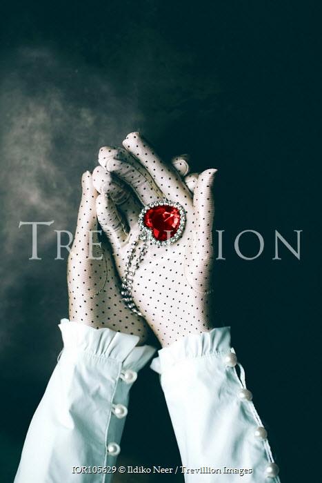 Ildiko Neer Woman holding heart pendant necklace in spotty gloves