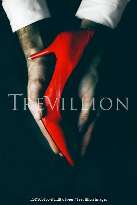 Ildiko Neer Red high heel in man's hands