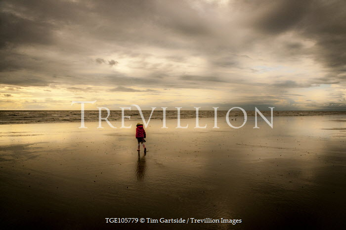 Tim Gartside YOUNG GIRL WALKING ON SANDY BEACH Children