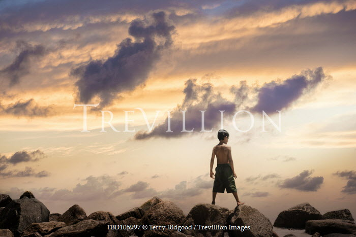 Terry Bidgood LITTLE BOY ON ROCKS BY SEA AT SUNSET Children