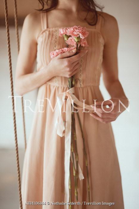 Nathalie Seiferth WOMAN IN BEIGE DRESS HOLDING PINK FLOWERS Women