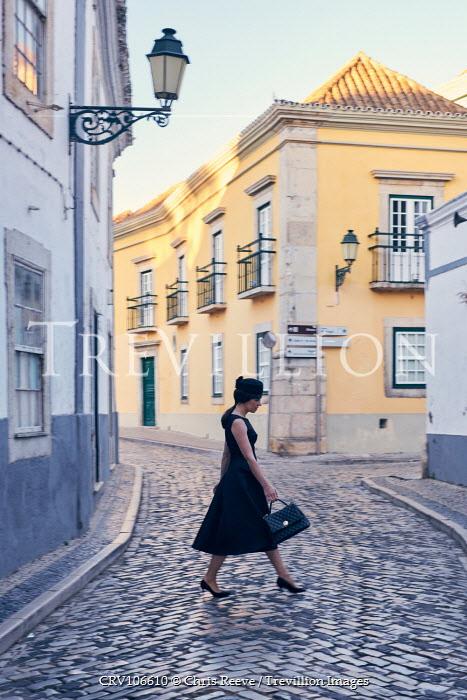 Chris Reeve Woman walking in cobbled street Women
