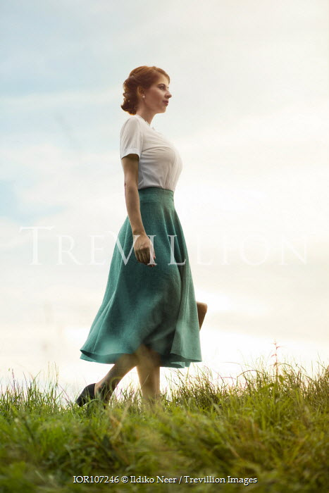 Ildiko Neer Vintage woman walking in grass with suitcase