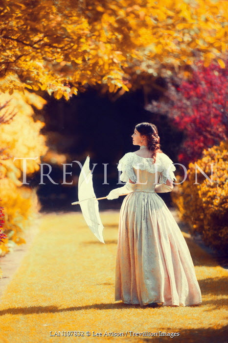 Lee Avison victorian woman in an autumn garden victorian,woman,walking,outside,outdoors,ball gown,evening dress,dress,bussle,19th century,1800s,alone,one person,full length,sunny,sunshine,autumn,fall,autumnal,parasol,back,rear view,lawn,garden,profile,brunette,wealthy,grounds Women