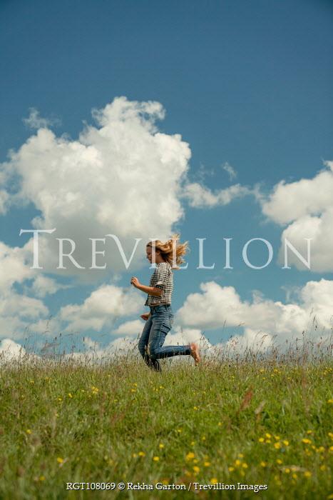 Rekha Garton GIRL IN JEANS RUNNING IN SUMMERY COUNTRYSIDE Women