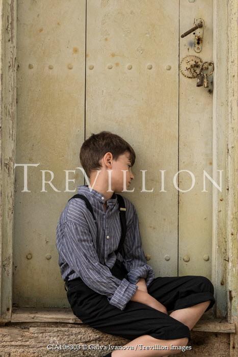 Galya Ivanova RETRO BOY LEANING AGAINST WOODEN DOOR Children