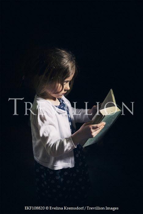 Evelina Kremsdorf Little girl reading in darkness Children