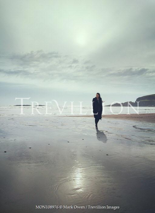 Mark Owen Woman walking on sandy wintry beach Women