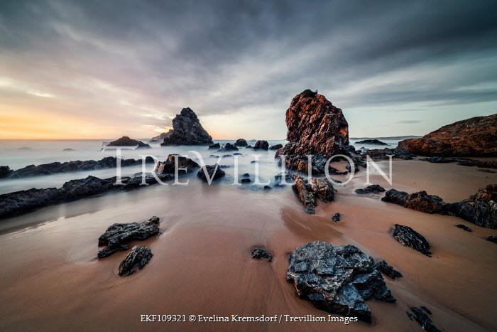 Evelina Kremsdorf ROCKS ON SANDY BEACH AT SUNSET Seascapes/Beaches