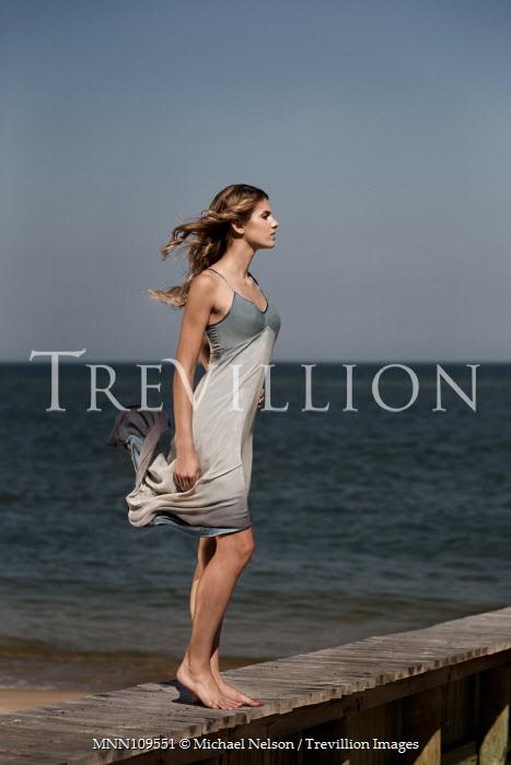 Michael Nelson Girl stood on jetty by sea Women