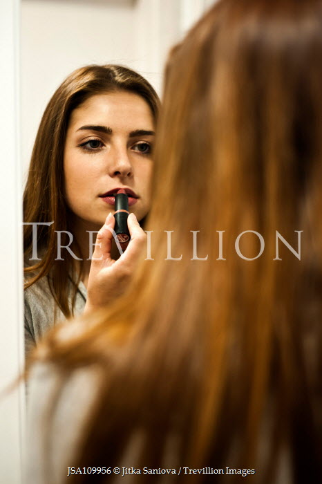 Jitka Saniova Girl applying lipstick in mirror Women