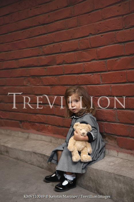 Kerstin Marinov LITTLE GIRL HUGGING TEDDY SITTING IN STREET Children