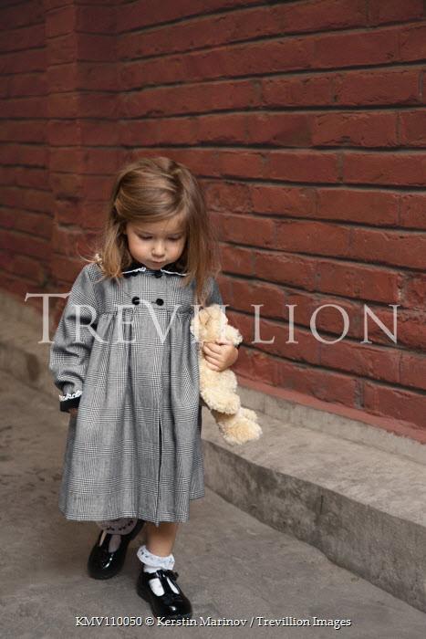 Kerstin Marinov LITTLE GIRL WALKING WITH TEDDY IN STREET Children
